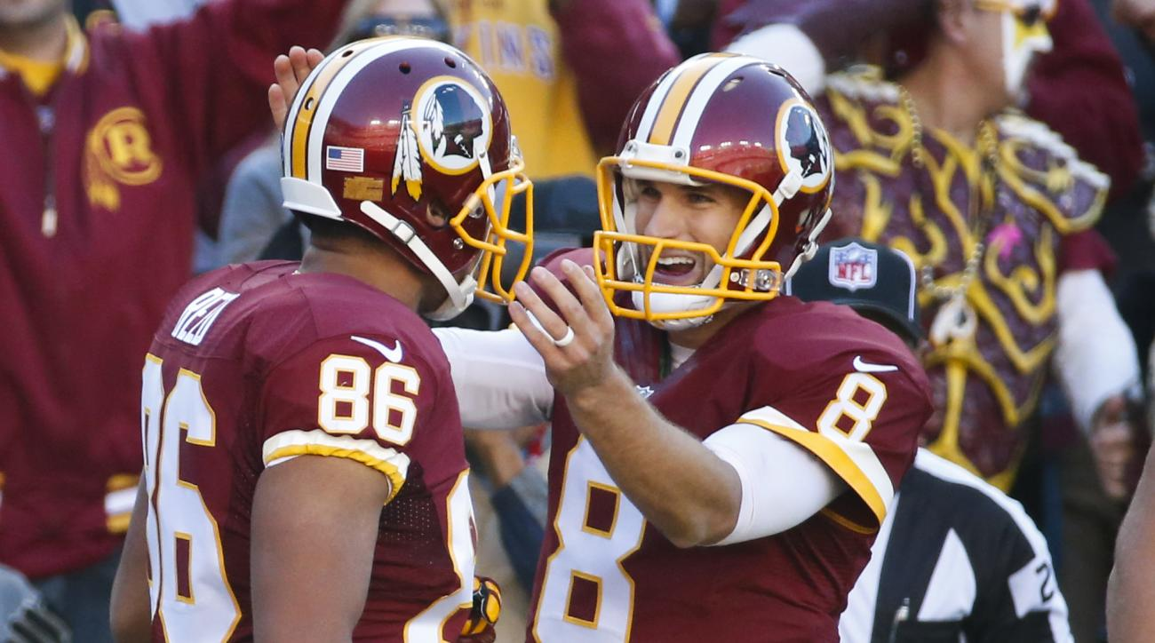 Washington Redskins quarterback Kirk Cousins (8) congratulates teammate tight end Jordan Reed (86) after his touchdown during the first half of an NFL football game against the New Orleans Saints in Landover, Md., Sunday, Nov. 15, 2015. (AP Photo/Alex Bra