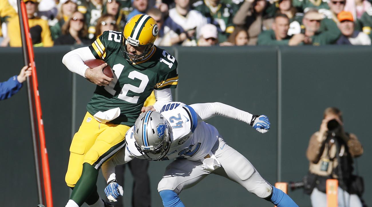 Green Bay Packers' Aaron Rodgers runs for a first down past Detroit Lions' Isa Abdul-Quddus during the first half of an NFL football game Sunday, Nov. 15, 2015, in Green Bay, Wis. (AP Photo/Morry Gash)