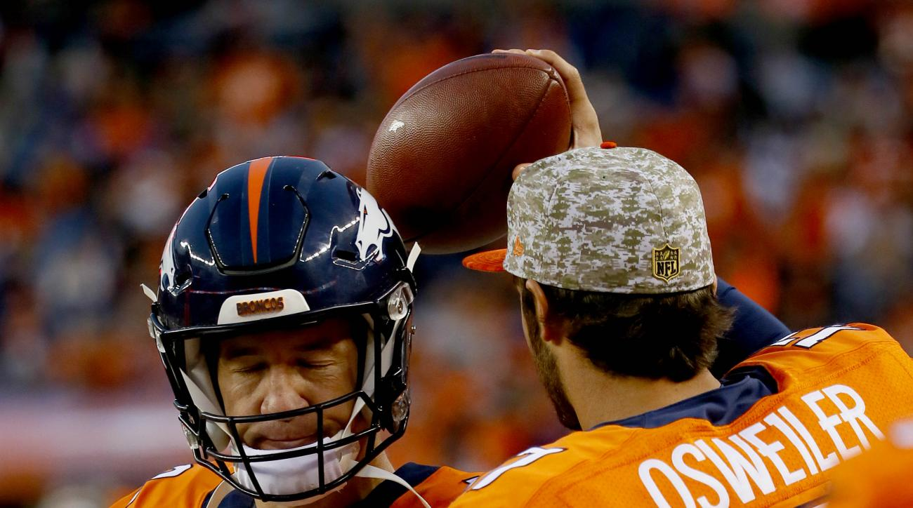 Denver Broncos quarterback Peyton Manning (18) talks with backup Brock Osweiler (17) after coming out of the game during the second half of an NFL football game against the Kansas City Chiefs, Sunday, Nov. 15, 2015, in Denver. (AP Photo/Jack Dempsey)