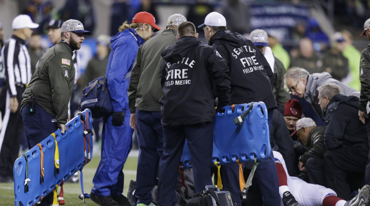 Backboards are brought in to take injured Arizona Cardinals guard Mike Iupati off the field after a play against the Seattle Seahawks during the first half of an NFL football game, Sunday, Nov. 15, 2015, in Seattle. (AP Photo/Stephen Brashear)