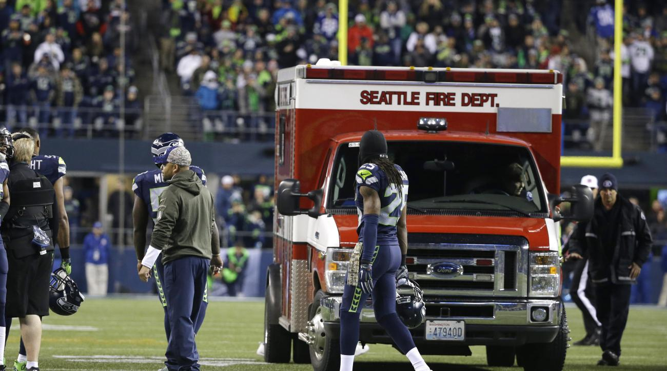 An ambulance is brought in to take injured Arizona Cardinals guard Mike Iupati off the field, during the first half of the Cardinals' NFL football game against the Seattle Seahawks on Sunday, Nov. 15, 2015, in Seattle. (AP Photo/Elaine Thompson)