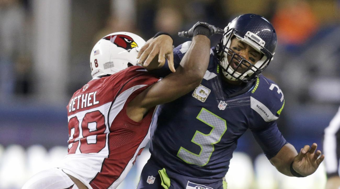 Seattle Seahawks quarterback Russell Wilson (3) is hit by Arizona Cardinals cornerback Justin Bethel just after getting a pass off during the second half of an NFL football game, Sunday, Nov. 15, 2015, in Seattle. (AP Photo/Stephen Brashear)