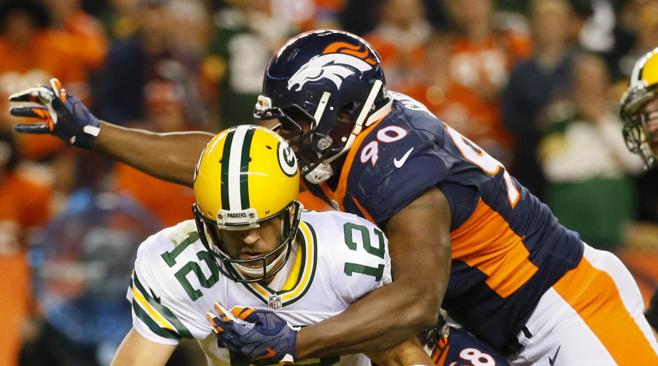 FILE - In this Sunday, Nov. 1, 2015 file photo, Green Bay Packers quarterback Aaron Rodgers (12) is sacked by Denver Broncos defensive end Antonio Smith (90) and outside linebacker Von Miller (58) during the second half of an NFL football game in Denver.