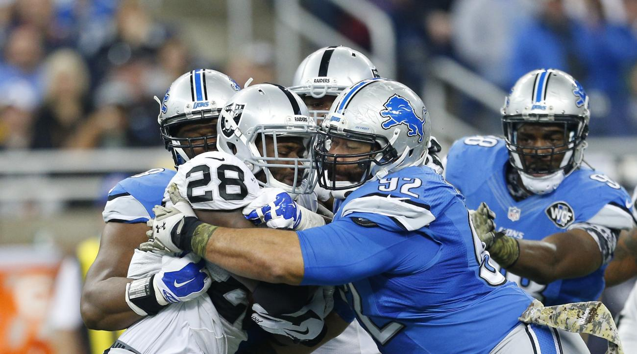 Detroit Lions defensive tackle Haloti Ngata (92) takes down Oakland Raiders running back Latavius Murray (28) during the first half of an NFL football game, Sunday, Nov. 22, 2015, in Detroit. (AP Photo/Rick Osentoski)