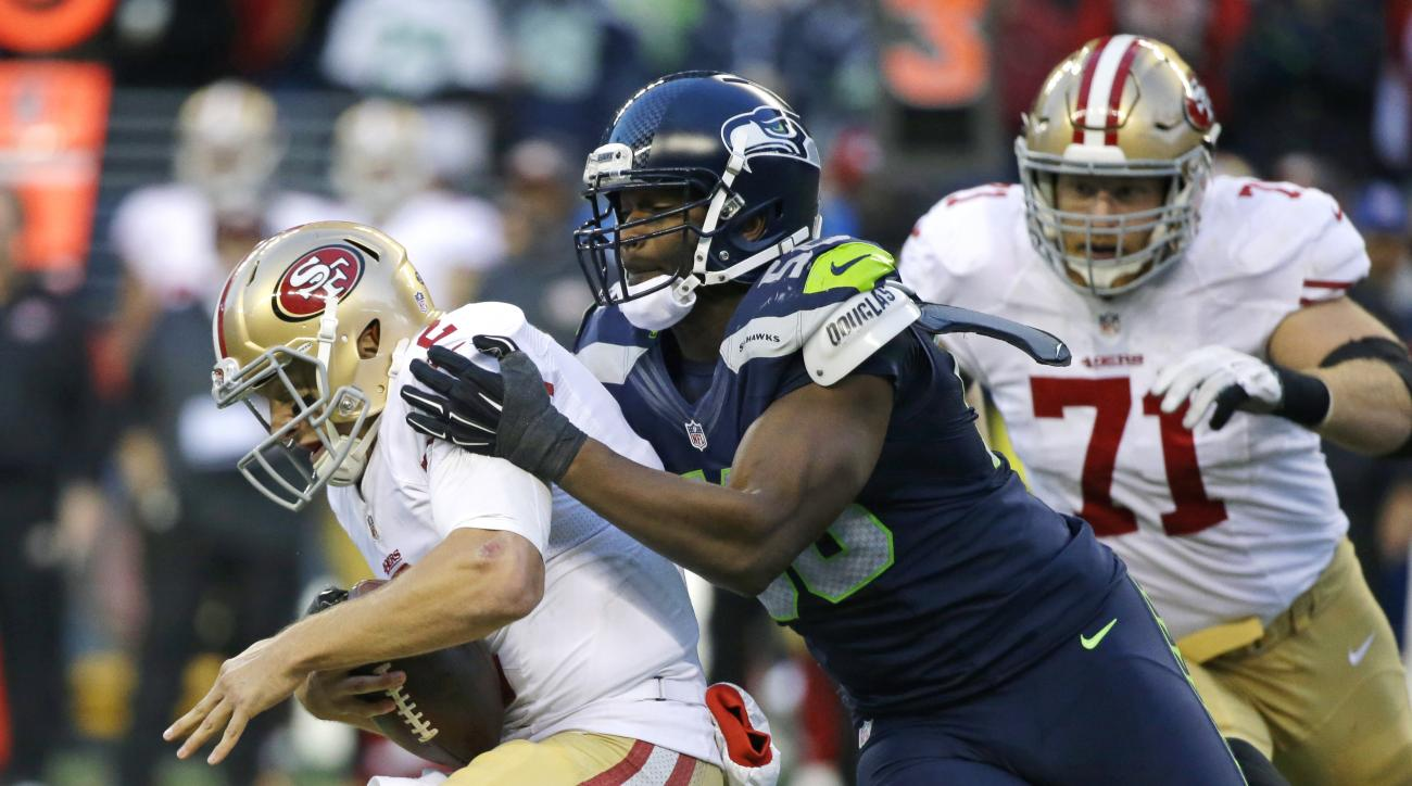 Seattle Seahawks defensive end Cliff Avril, center, sacks San Francisco 49ers quarterback Blaine Gabbert, left, in the second half of an NFL football game, Sunday, Nov. 22, 2015, in Seattle. (AP Photo/Elaine Thompson)