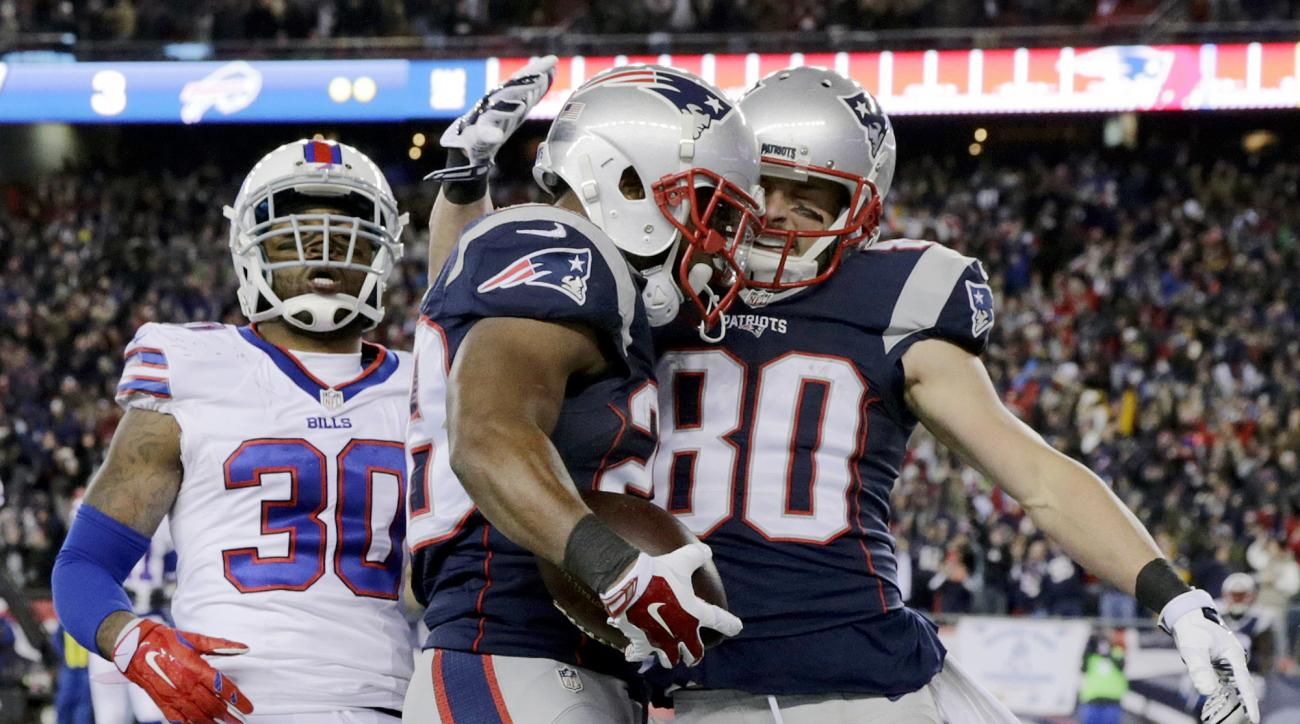 New England Patriots running back James White, center, celebrates his touchdown with wide receiver Danny Amendola (80) in front of Buffalo Bills safety Bacarri Rambo (30) in the first half of an NFL football game, Monday, Nov. 23, 2015, in Foxborough, Mas