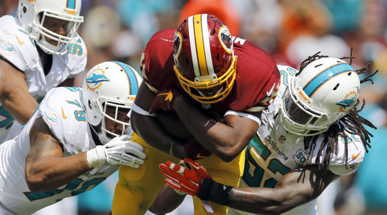 FILE - In this Sept. 13, 2015 file photo, Miami Dolphins defensive end Derrick Shelby (79) and middle linebacker Kelvin Sheppard (52) tackle Washington Redskins running back Alfred Morris (46) during the first half of an NFL football game in Landover, Md.