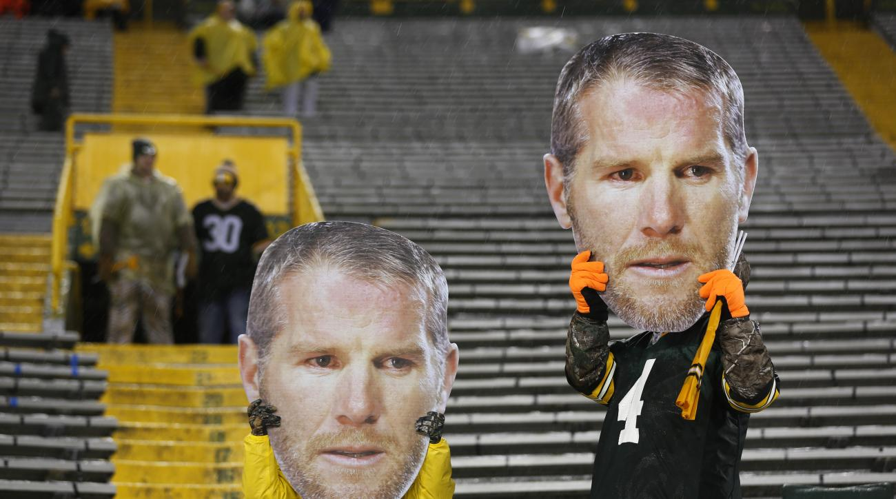 Fans hold up former Green Bay Packers quarterback Brett Favre masks before an NFL football game between the Green Bay Packers and the Chicago Bears Thursday, Nov. 26, 2015, in Green Bay, Wis. Favre is being honored during a ceremony at halftime. (AP Photo