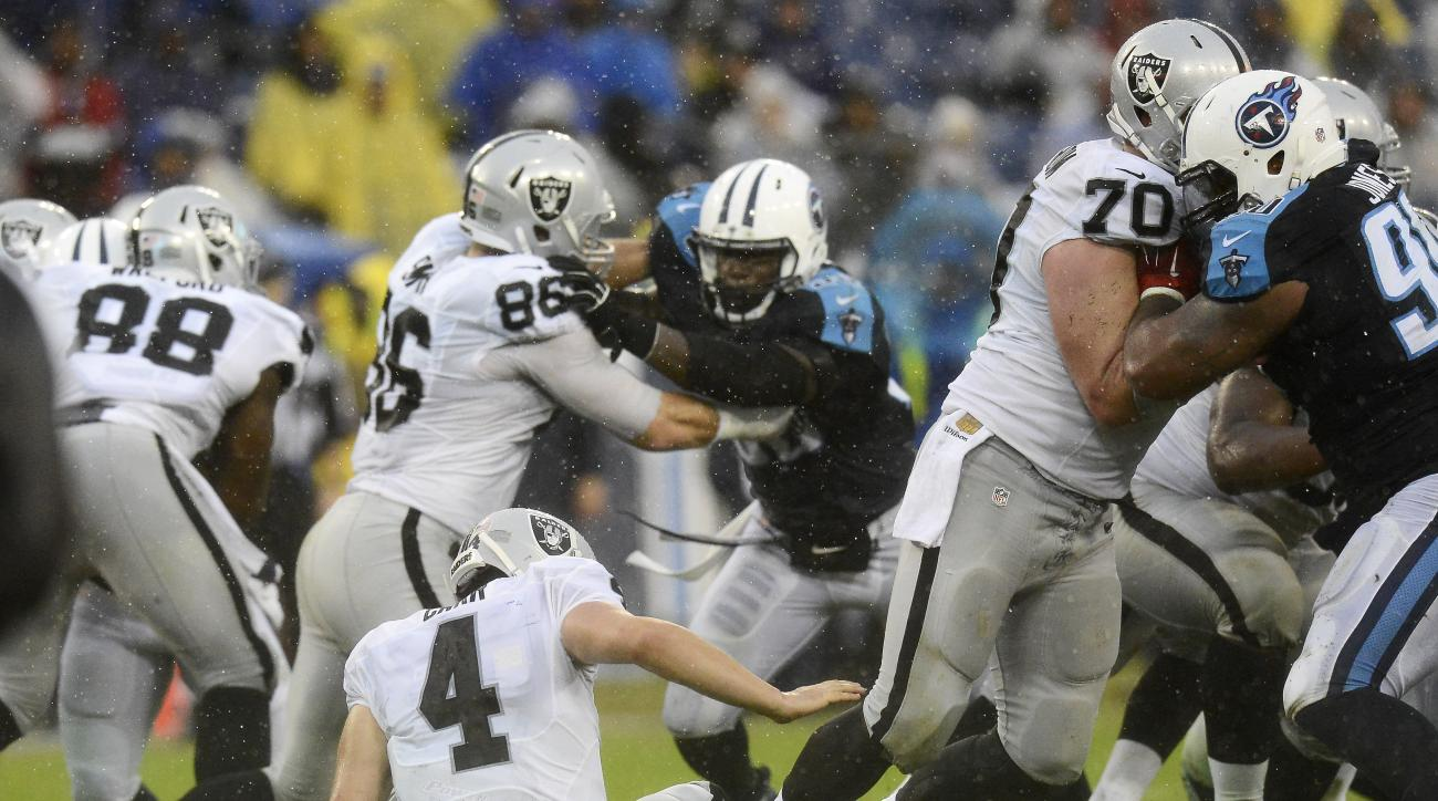 Oakland Raiders quarterback Derek Carr (4) fumbles a snap in the second half of an NFL football game against the Tennessee Titans Sunday, Nov. 29, 2015, in Nashville, Tenn. The Titans recovered the ball. (AP Photo/Mark Zaleski)