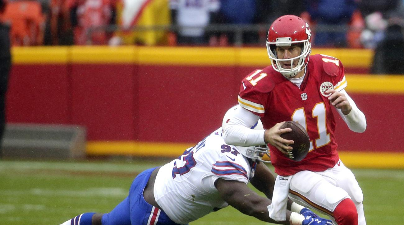 Kansas City Chiefs quarterback Alex Smith (11) runs past a tackle attempt by Buffalo Bills defensive tackle Corbin Bryant (97) during the first half of an NFL football game in Kansas City, Mo., Sunday, Nov. 29, 2015. (AP Photo/Charlie Riedel)