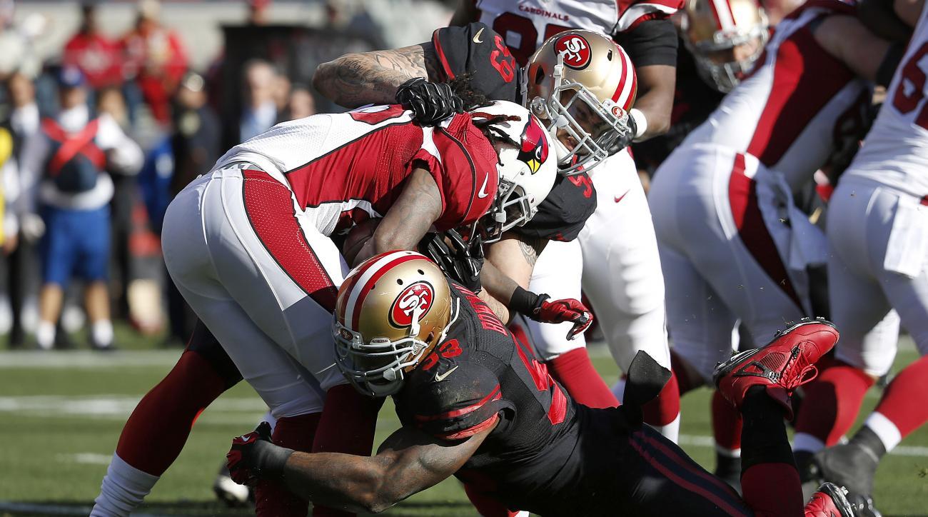 Arizona Cardinals running back Chris Johnson, center, is tackled by San Francisco 49ers linebacker Aaron Lynch (59) and linebacker NaVorro Bowman (53) during the first half of an NFL football game in Santa Clara, Calif., Sunday, Nov. 29, 2015. (AP Photo/T