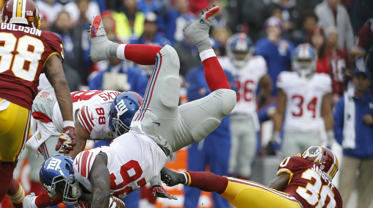 New York Giants running back Orleans Darkwa (26) is upended by Washington Redskins strong safety Kyshoen Jarrett (30) during the first half of an NFL football game in Landover, Md., Sunday, Nov. 29, 2015. (AP Photo/Patrick Semansky)