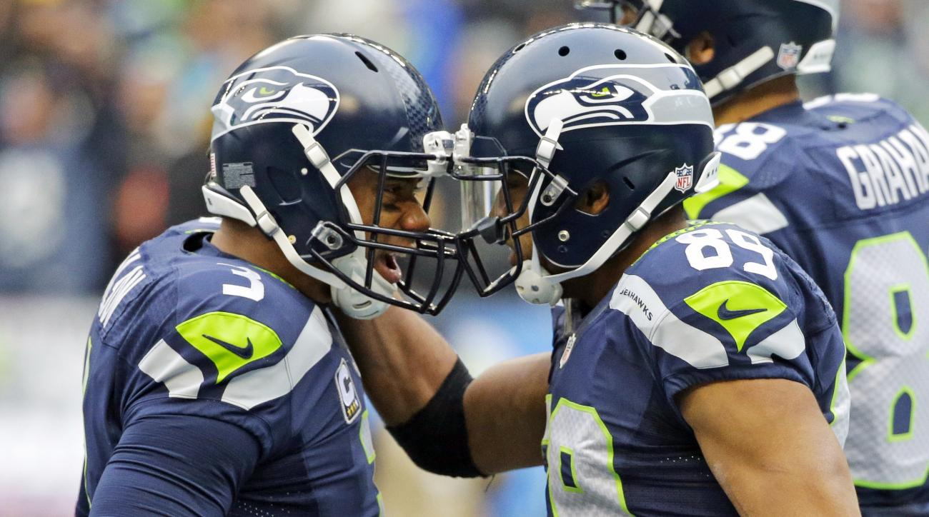 Seattle Seahawks quarterback Russell Wilson, left, celebrates with wide receiver Doug Baldwin, right, after Wilson passed to Baldwin for a touchdown against the Pittsburgh Steelers in the first half of an NFL football game, Sunday, Nov. 29, 2015, in Seatt