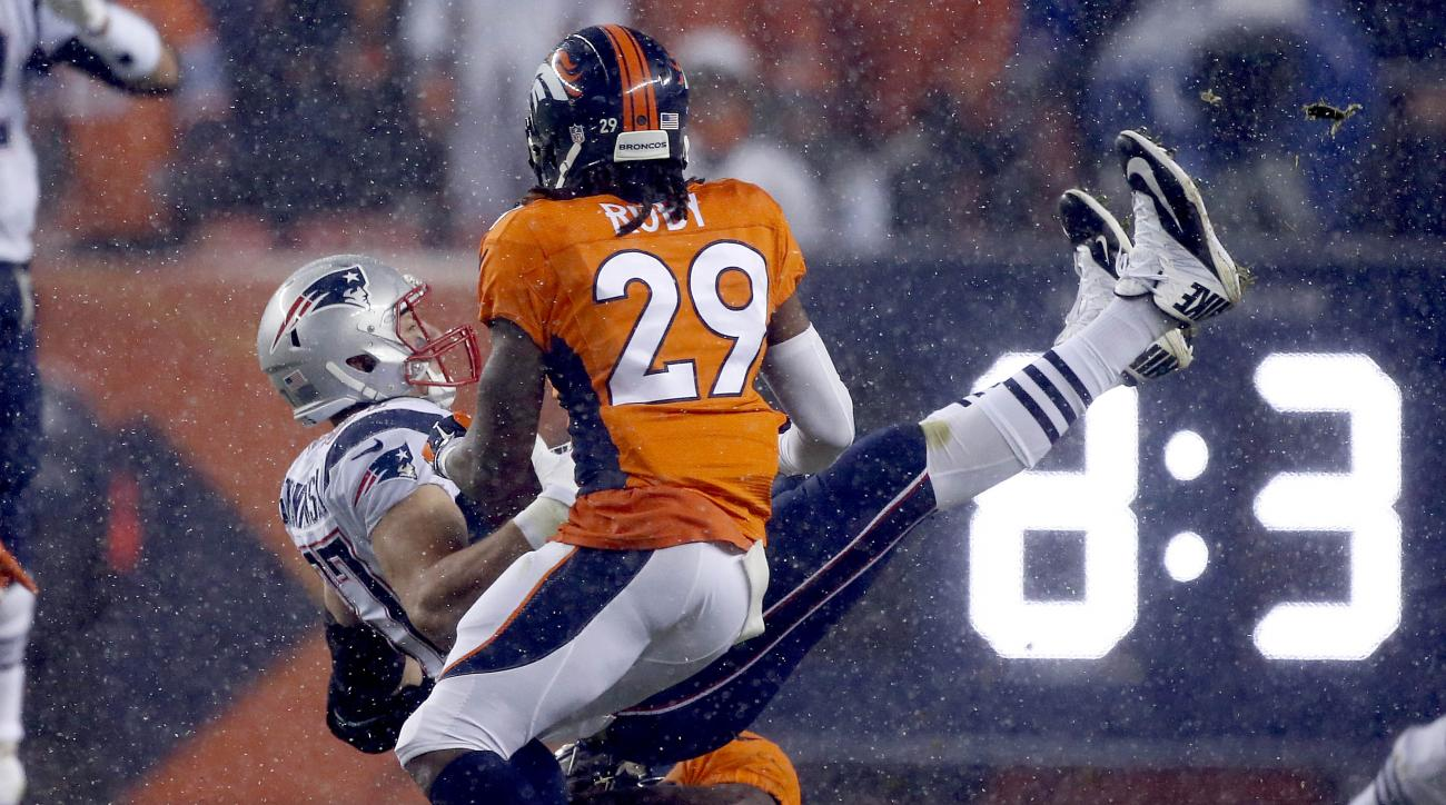 New England Patriots tight end Rob Gronkowski (87) is up-ended by Denver Broncos free safety Darian Stewart as free safety Bradley Roby (29) looks on during the first half of an NFL football game, Sunday, Nov. 29, 2015, in Denver. (AP Photo/Joe Mahoney)