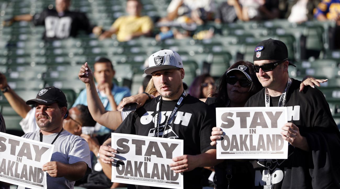 FILE - In this Aug. 14, 2015, file photo, Oakland Raiders fans hold up signs for the team to stay in Oakland before an NFL preseason football game between the Raiders and the St. Louis Rams in Oakland, Calif. The NFL's owners could take a significant step