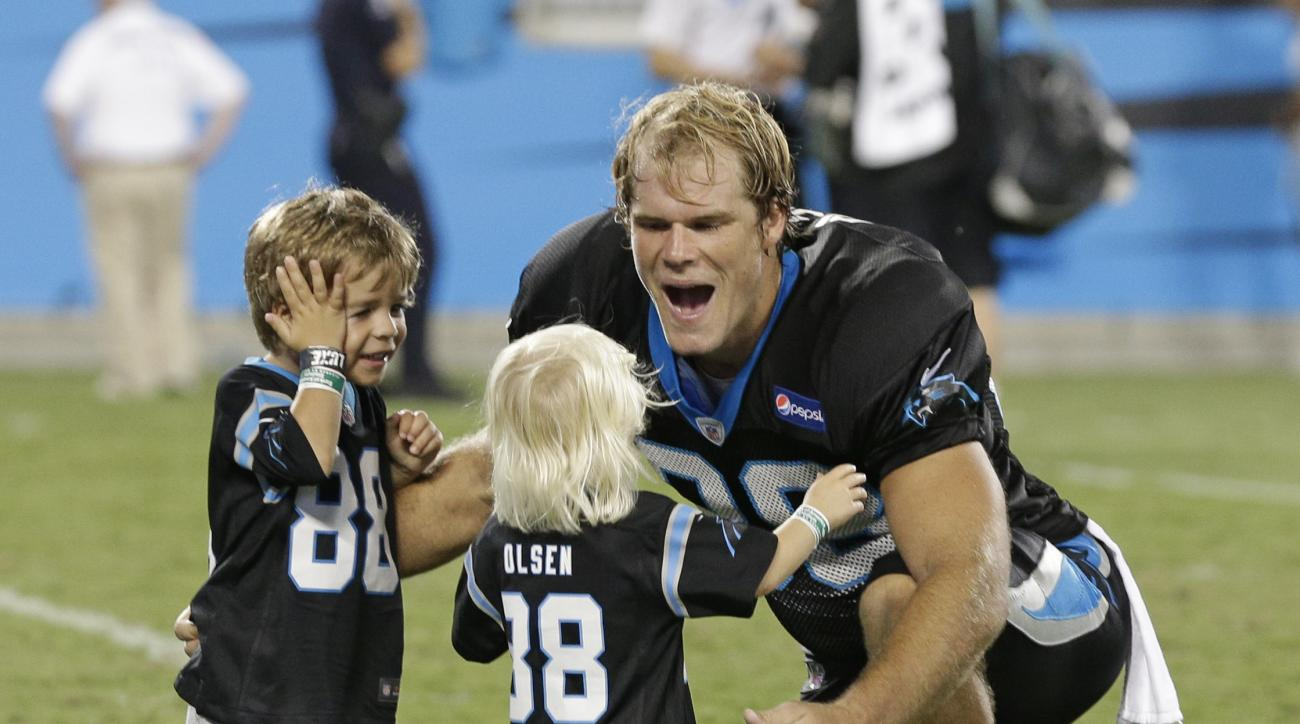 FILE - In this Aug. 7, 2015, file photo, Carolina Panthers' Greg Olsen, right, greets his children, Tate, left, and Talbot, center, during the annual Fan Fest at the NFL football team's training camp in Charlotte, N.C. When Carolina tight end Greg Olsen a