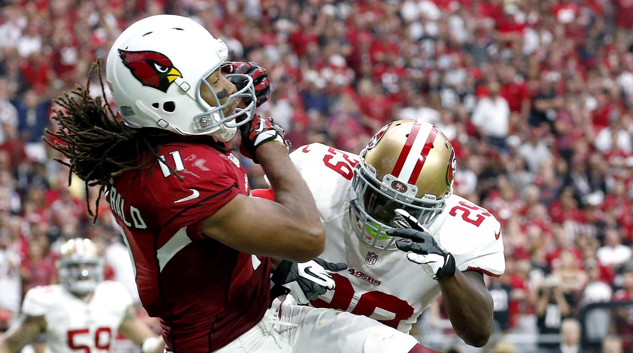 FILE - In this Sept. 27, 2015, file photo, Arizona Cardinals wide receiver Larry Fitzgerald (11) scores a touchdown as San Francisco 49ers strong safety Jaquiski Tartt (29) defends during an NFL football game in Glendale, Ariz.  Fitzgerald is on the brink