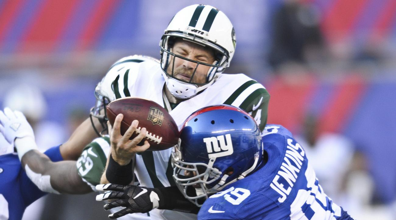 New York Jets quarterback Ryan Fitzpatrick (14) is sacked by New York Giants' Cullen Jenkins (99) during the first half of an NFL football game Sunday, Dec. 6, 2015, in East Rutherford, N.J. (AP Photo/Bill Kostroun)
