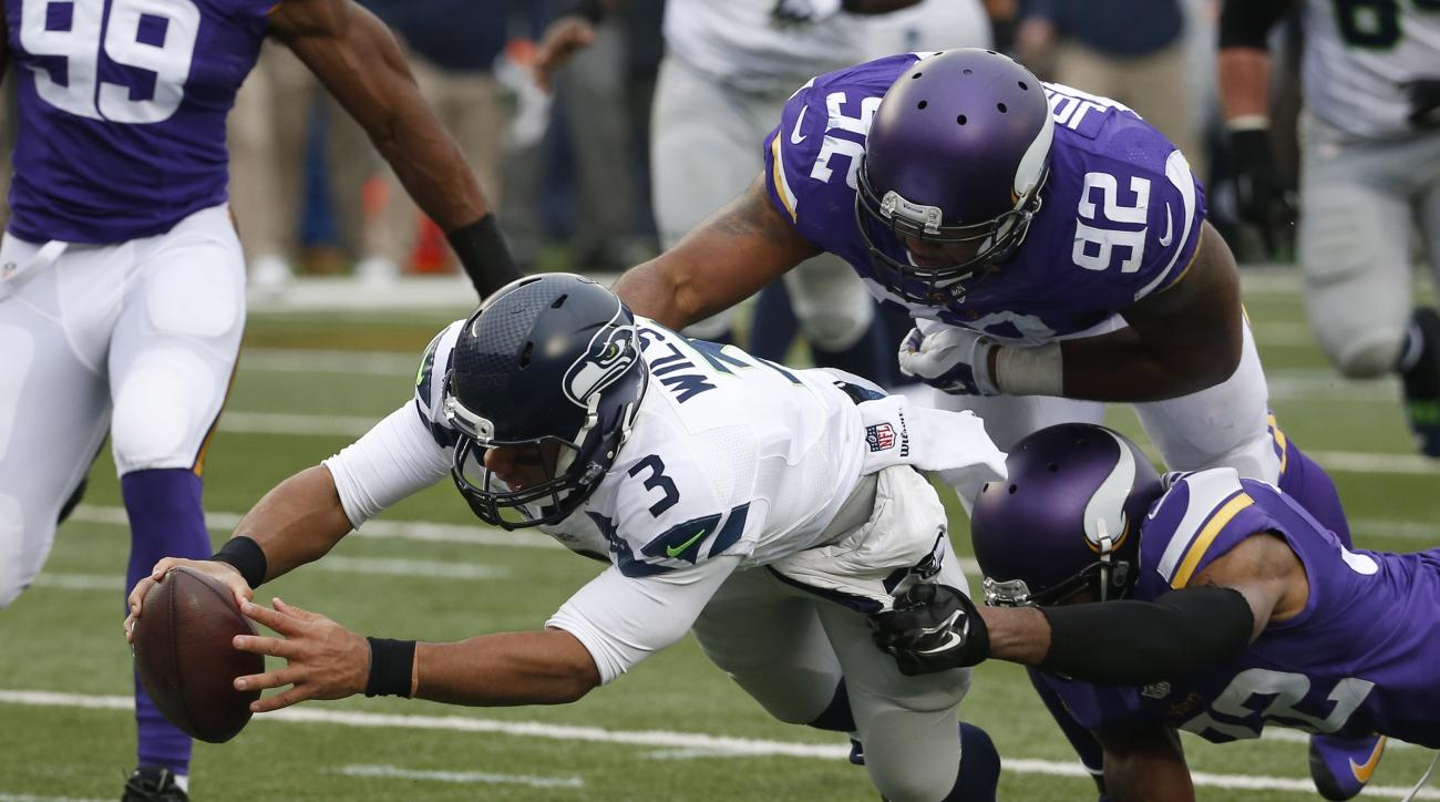 Seattle Seahawks quarterback Russell Wilson (3) dives for a eight-yard touchdown run as Minnesota Vikings cornerback Antone Exum (32) defensive tackle Tom Johnson (92) try to bring him down in the first half of an NFL football game Sunday, Dec. 6, 2015 in