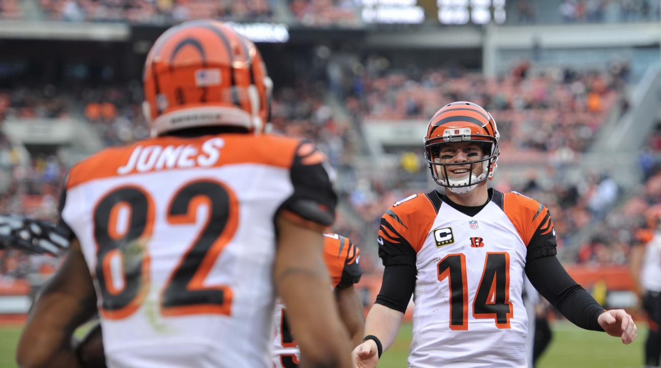 Cincinnati Bengals quarterback Andy Dalton (14) smiles as he goes to congratulate wide receiver Marvin Jones (82) after a 21-yard touchdown in the second half of an NFL football game against the Cleveland Browns, Sunday, Dec. 6, 2015, in Cleveland. (AP Ph