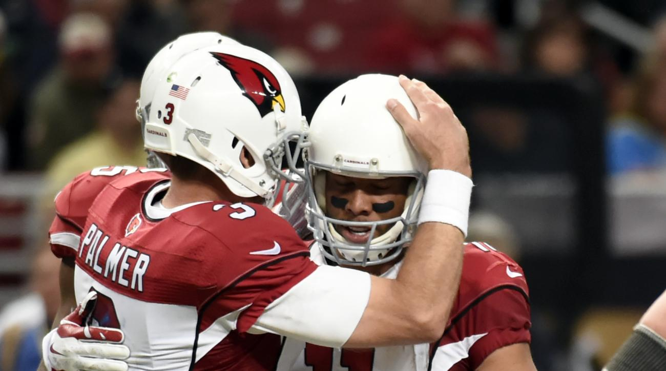 Arizona Cardinals wide receiver Larry Fitzgerald, right, is congratulated by quarterback Carson Palmer after catching a pass during the fourth quarter of an NFL football game against the St. Louis Ram on Sunday, Dec. 6, 2015, in St. Louis. With the recept