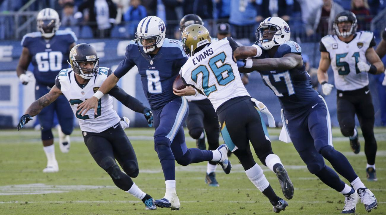Tennessee Titans quarterback Marcus Mariota (8) gets past Jacksonville Jaguars defenders Dwayne Gratz (27) and Josh Evans (26) as Titans wide receiver Dorial Green-Beckham (17) blocks as Mariota runs 87 yards for a touchdown in the second half of an NFL f