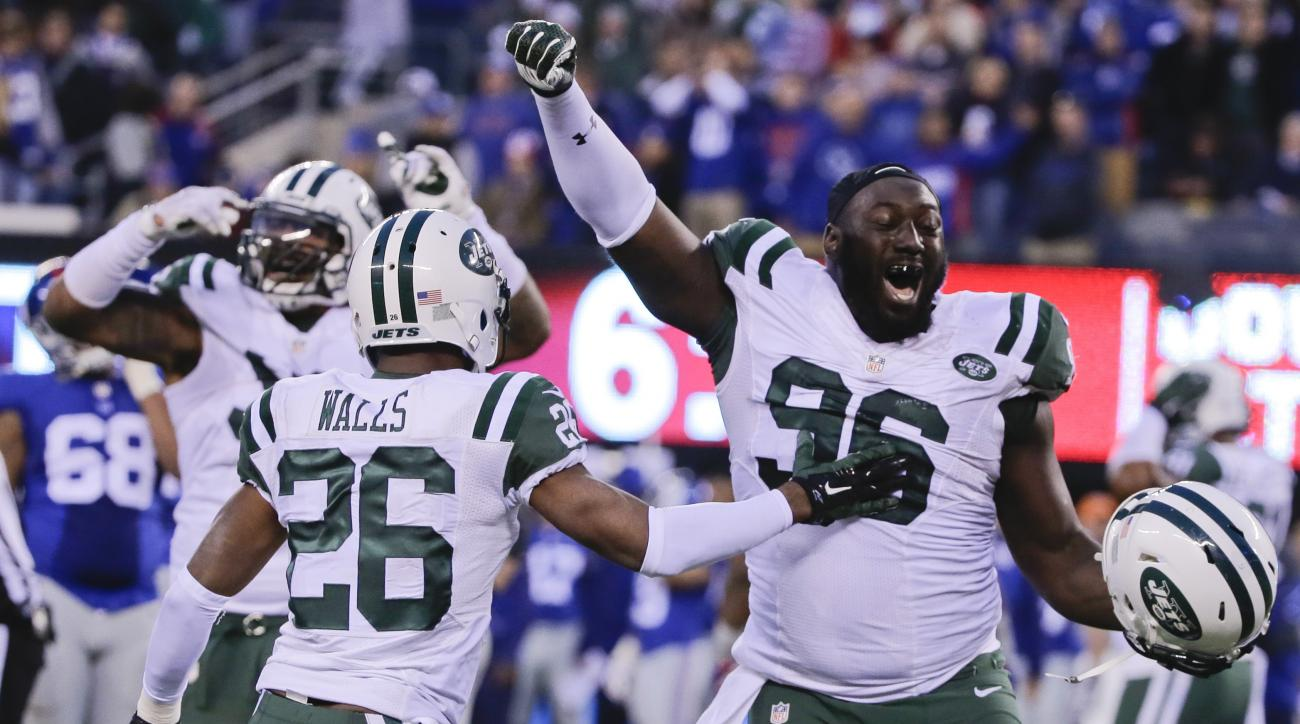 New York Jets' Muhammad Wilkerson (96) and Darrin Walls (26) celebrate after overtime of an NFL football game against the New York Giants Sunday, Dec. 6, 2015, in East Rutherford, N.J. The Jets won 23-20. (AP Photo/Julie Jacobson)