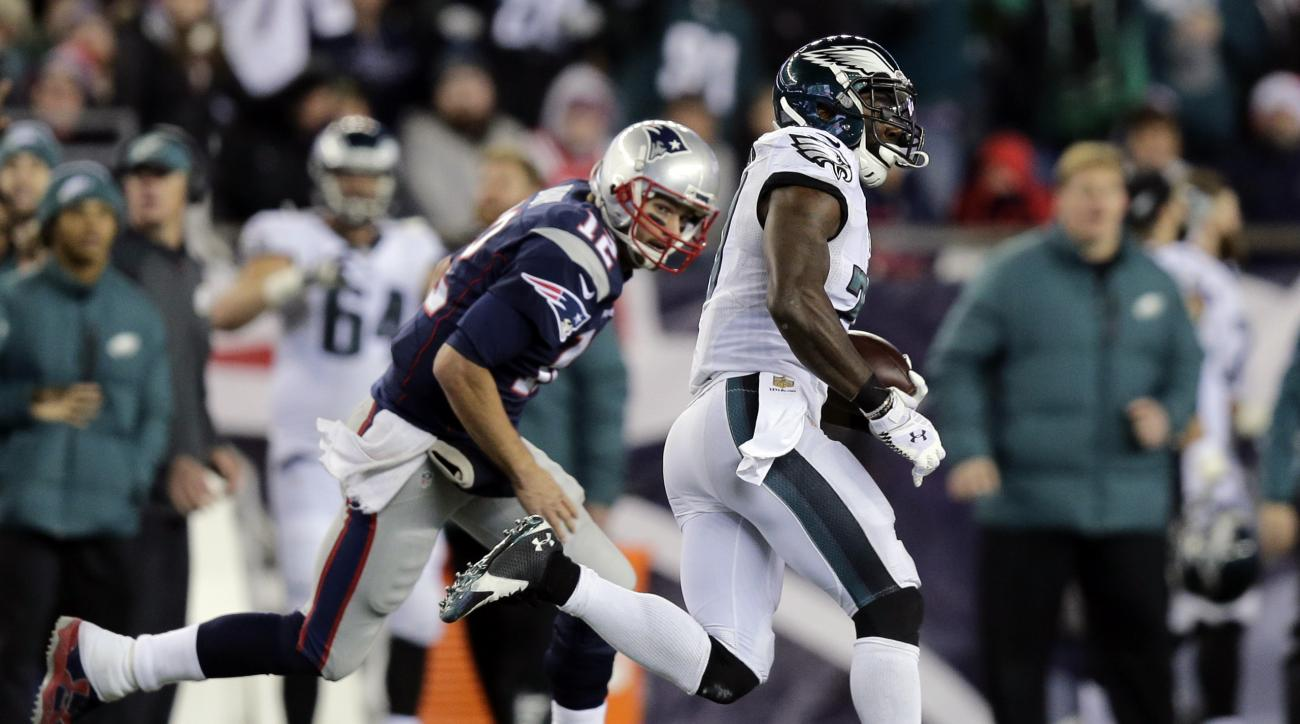 Philadelphia Eagles safety Malcolm Jenkins runs past New England Patriots quarterback Tom Brady (12) with a 100-yard interception return for a touchdown during the second half of an NFL football game, Sunday, Dec. 6, 2015, in Foxborough, Mass. (AP Photo/C
