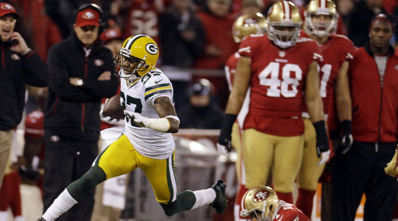FILE - In this Jan. 12, 2013 file photo, Green Bay Packers cornerback Sam Shields (37) returns an interception for a touchdown as he dives past San Francisco 49ers quarterback Colin Kaepernick (7) during the first quarter of an NFC divisional playoff NFL