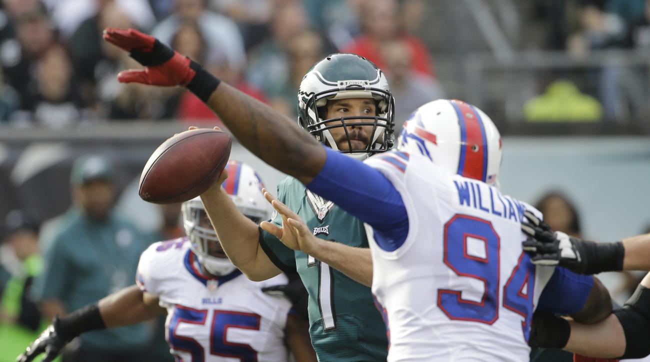 Philadelphia Eagles' Sam Bradford, center, passes between Buffalo Bills' Mario Williams (94) and Jerry Hughes (55) during the first half of an NFL football game against the Buffalo Bills, Sunday, Dec. 13, 2015, in Philadelphia. (AP Photo/Matt Rourke)