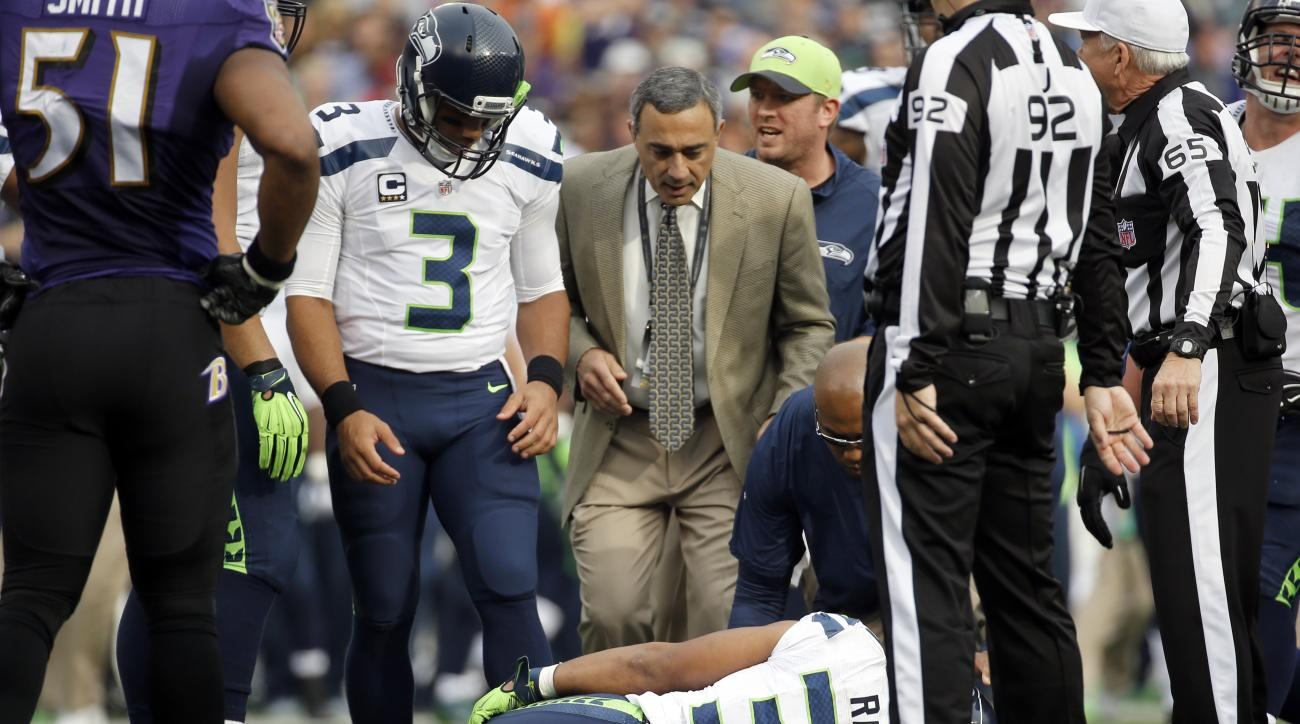Seattle Seahawks quarterback Russell Wilson (3) looks at an injured Seahawks running back Thomas Rawls (34) during the first half an NFL football game against the Baltimore Ravens, Sunday, Dec. 13, 2015, in Baltimore. (AP Photo/Patrick Semansky)