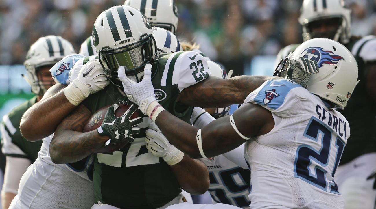 New York Jets' Stevan Ridley (22) is tackled by Tennessee Titans' Da'Norris Searcy (21) and DaQuan Jones (90) during the first half of an NFL football game Sunday, Dec. 13, 2015, in East Rutherford, N.J.  (AP Photo/Julio Cortez)