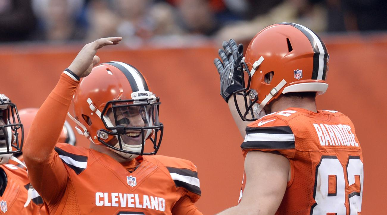 Cleveland Browns quarterback Johnny Manziel (2) celebrates with Gary Barnidge (82) after throwing a 2-yard pass to Barnidge for a touchdown during the second half of an NFL football game against the San Francisco 49ers, Sunday, Dec. 13, 2015, in Cleveland