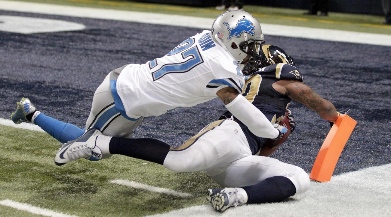 St. Louis Rams running back Todd Gurley, bottom, scores past Detroit Lions free safety Glover Quin on a 15-yard run during the fourth quarter of an NFL football game Sunday, Dec. 13, 2015, in St. Louis. (AP Photo/Tom Gannam)