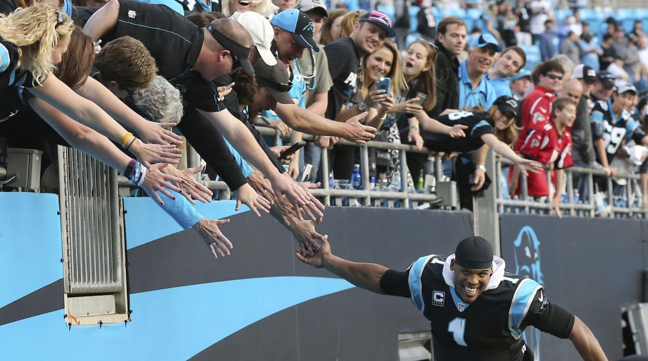 Carolina Panthers quarterback Cam Newton celebrates with fans after defeating the Atlanta Falcons 38-0 in an NFL football game in Charlotte, N.C., Sunday, Dec. 13, 2015. (Curtis Compton/Atlanta Journal-Constitution via AP)  MARIETTA DAILY OUT; GWINNETT DA
