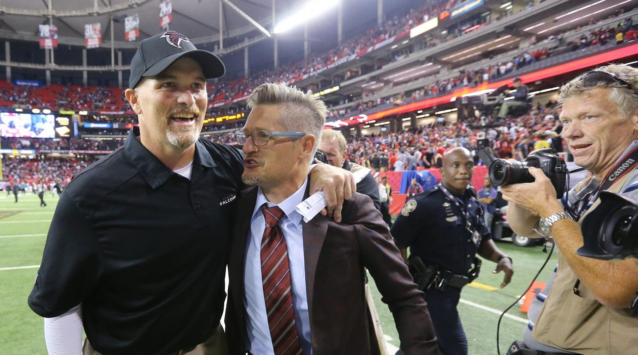 FILE - In this Monday, Sept. 14, 2015,  file photo, Atlanta Falcons head coach Dan Quinn, left,  celebrates winning his first NFL game as a head coach with general manager Thomas Dimitroff after an NFL football game, in Atlanta. No one is facing the heat