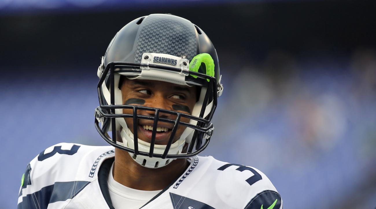 FILE - In this Dec. 13, 2015, file photo, Seattle Seahawks quarterback Russell Wilson (3) smiles during warms up before an NFL football game against the Baltimore Ravens, in Baltimore. Russell Wilson has it all put together. Johnny Manziel has been nothin