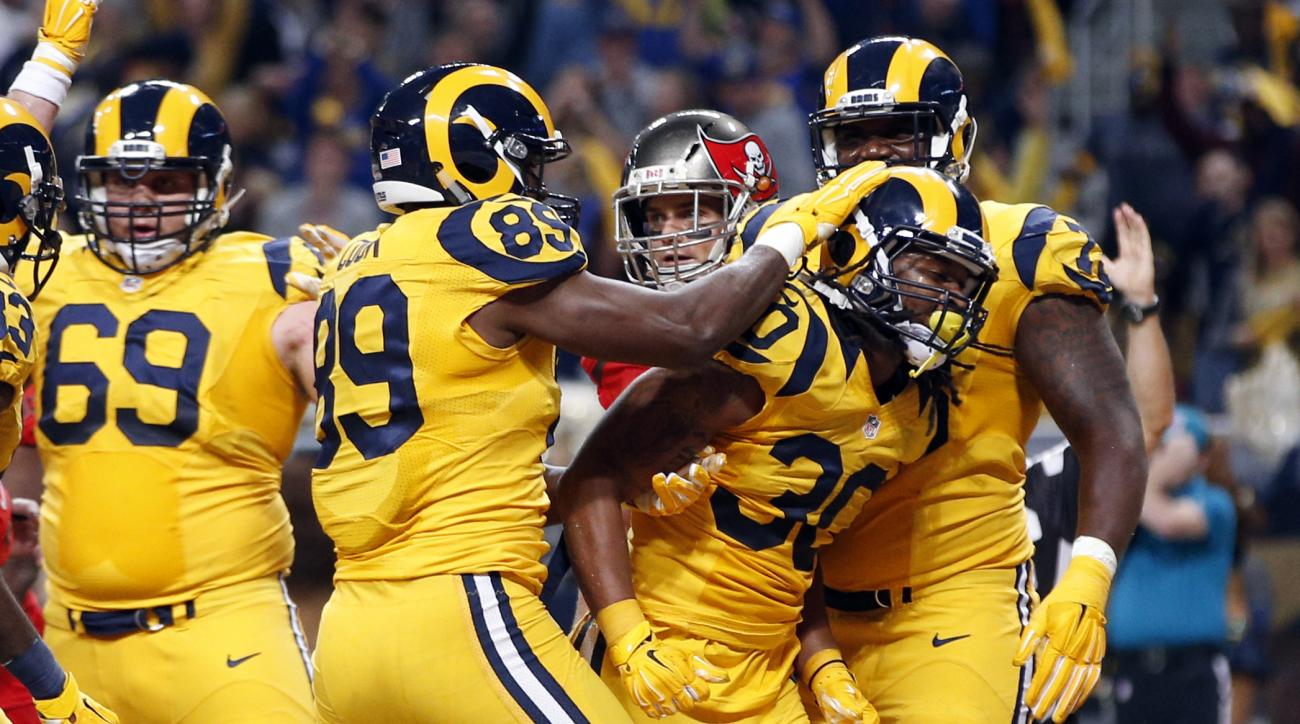 St. Louis Rams running back Todd Gurley (30) is congratulated by teammates after scoring on a 3-yard run during the second quarter of an NFL football game against the Tampa Bay Buccaneers on Thursday, Dec. 17, 2015, in St. Louis. (AP Photo/Billy Hurst)