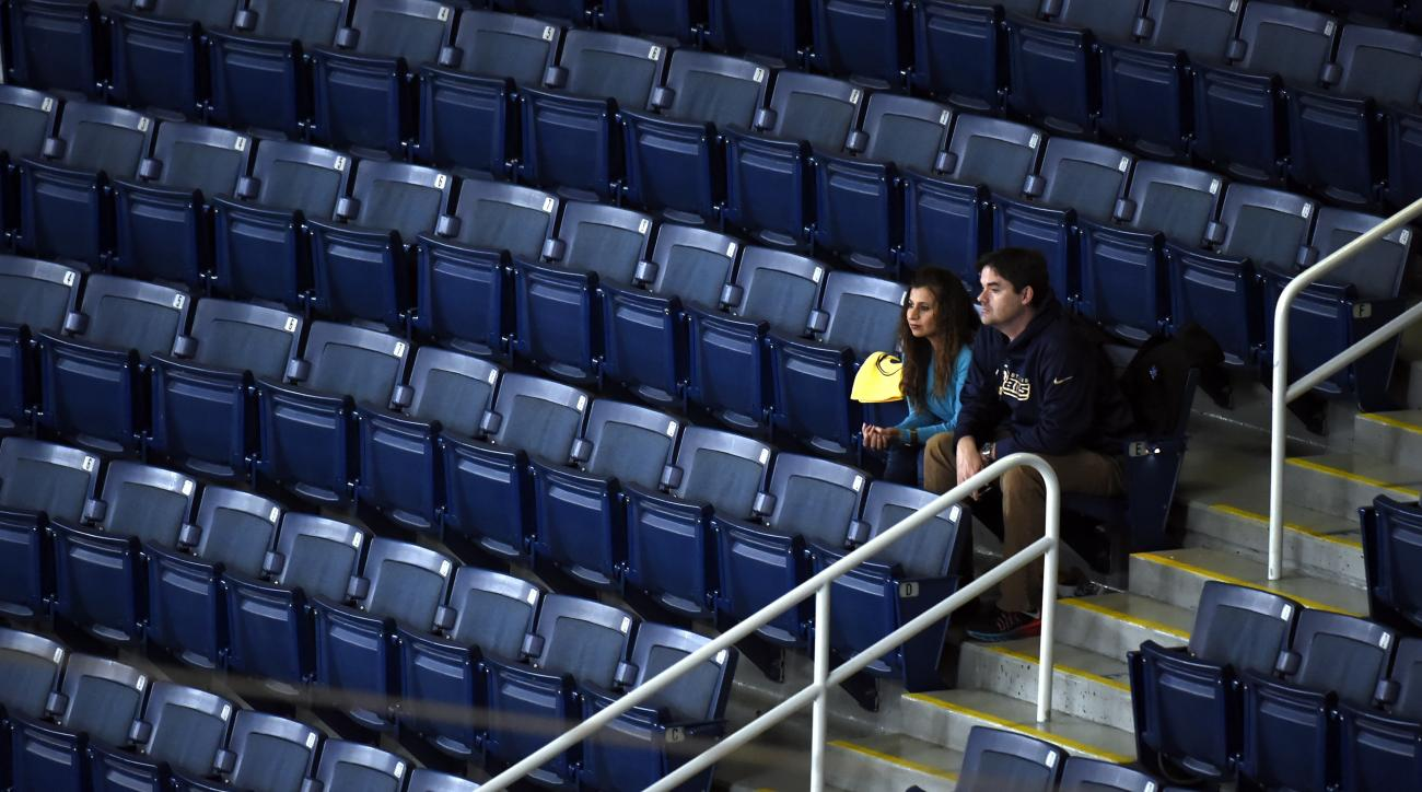 A few fans are surrounded by empty seats in a section of the stadium as the St. Louis Rams play the Tampa Bay Buccaneers during the third quarter of an NFL football game Thursday, Dec. 17, 2015, in St. Louis. The game could be the final home contest for t
