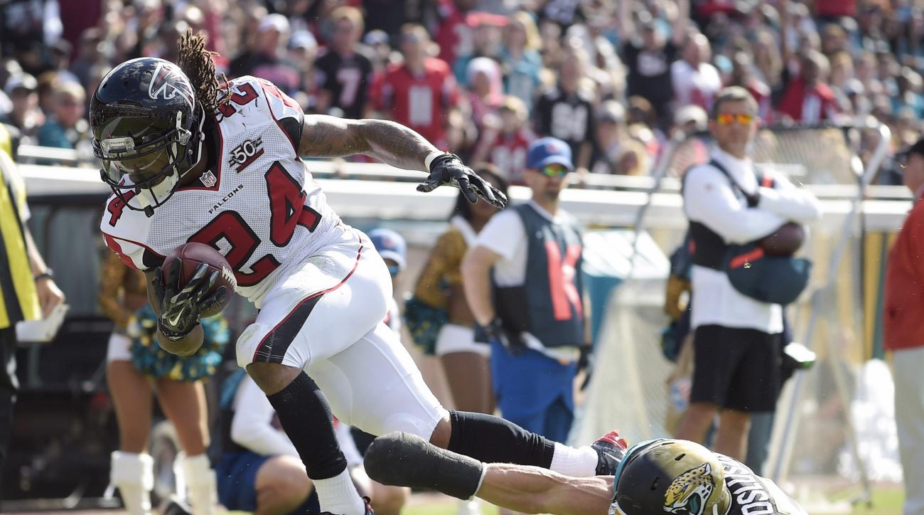 Atlanta Falcons running back Devonta Freeman (24) scores a touchdown on a 5-yard run past Jacksonville Jaguars middle linebacker Paul Posluszny, right, during the first half of an NFL football game in Jacksonville, Fla., Sunday, Dec. 20, 2015. (AP Photo/P