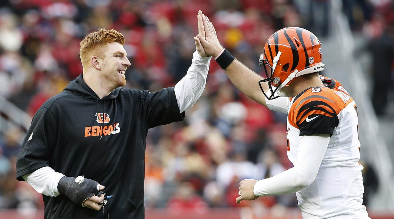Injured Cincinnati Bengals quarterback Andy Dalton, left, celebrates with quarterback AJ McCarron after the team scored a touchdown against the San Francisco 49ers during the first half of an NFL football game in Santa Clara, Calif., Sunday, Dec. 20, 2015