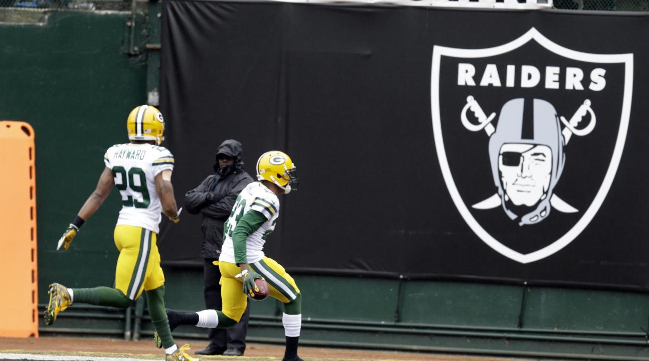 Green Bay Packers cornerback Damarious Randall, center, returns an interception for a touchdown against the Oakland Raiders during the first half of an NFL football game, Sunday, Dec. 20, 2015, in Oakland, Calif. (AP Photo/Ben Margot)