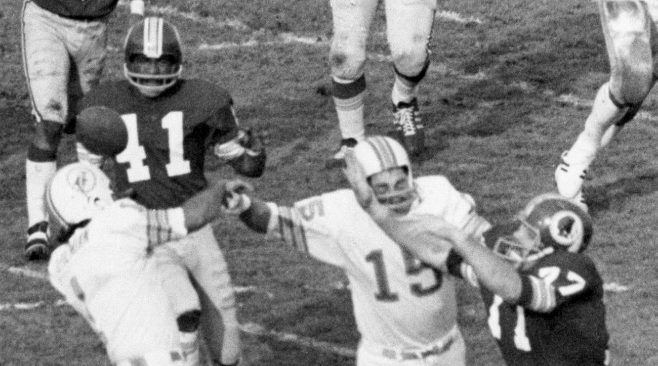 FILE - In this Jan. 14, 1973, file photo, Washington Redskins' Mike Bass (41) gets ball which deflected out of Miami Dolphins kicker Garo Yepremian's hands during NFL football's Super Bowl VII in Los Angeles. (AP Photo, File)