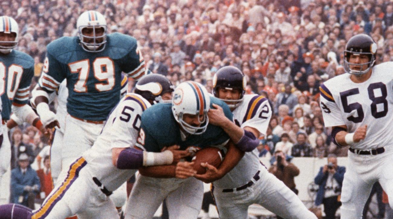 FILE - In this Jan. 13, 1974, file photo, Miami Dolphins' Larry Csonka drives between Minnesota Vikings' Jeff Siemon (50) and Paul Krause for one of his two touchdowns in the NFL football Super Bowl in Houston. Csonka was named MVP as Miami defeated the V