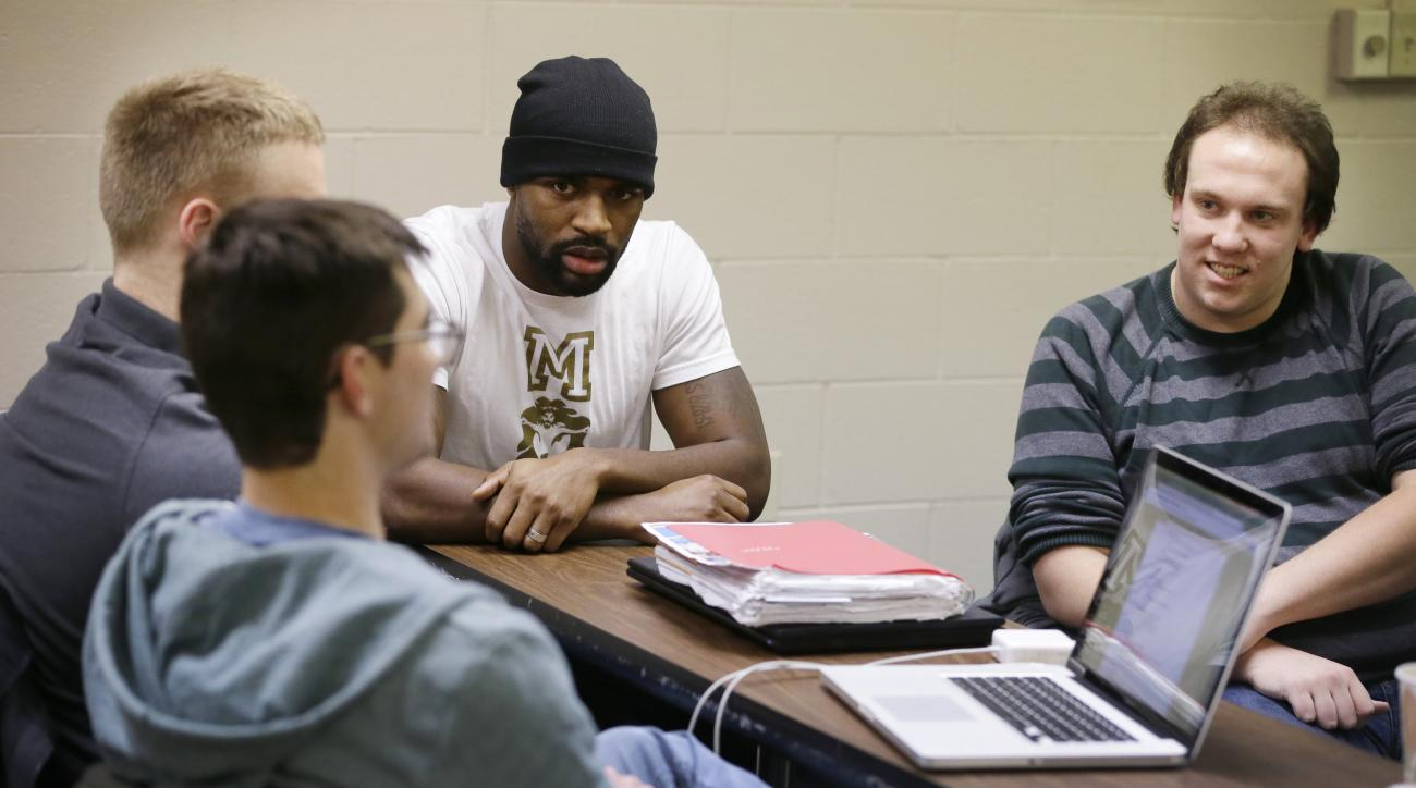 In a photo from Dec. 7, 2015, Detroit Lions NFL football defensive back Don Carey, center, listens with classmates John Syverson, left, and Brian Ault, right, at the Moody Theological Seminary and Graduate School in Plymouth, Mich. Carey takes two classes