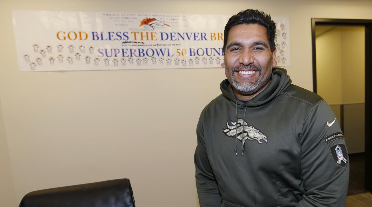 In this Wednesday, Dec. 16, 2015 photo, Denver Broncos team chaplain Luther Elliss poses for a photo in his office in the team's headquarters in Englewood, Colo. Elliss, once the highest-paid defensive tackle in the NFL before losing it all and going bank