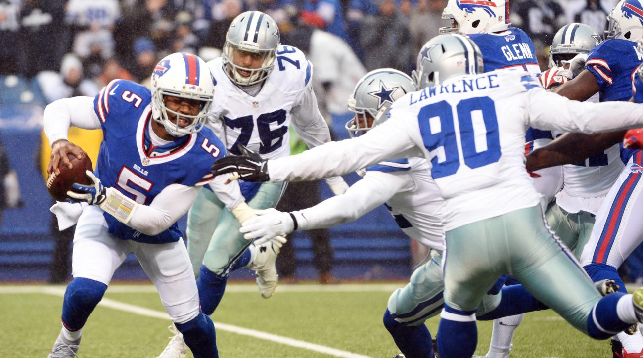 Buffalo Bills quarterback Tyrod Taylor (5) tries to get away from Dallas Cowboys defensive end Demarcus Lawrence (90) and strong safety Barry Church (42) during the second half of an NFL football game, Sunday, Dec. 27, 2015, in Orchard Park, N.Y. (AP Phot