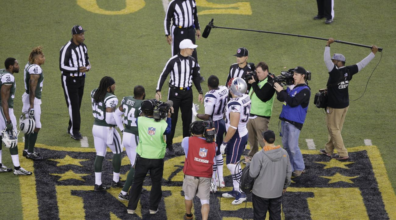 The officials meet New York Jets' Darrelle Revis (24), teammate Calvin Pryor (25) and New England Patriots' Matthew Slater (18) and teammate Rob Ninkovich (50) for the coin toss before the overtime period of an NFL football game between the New York Jets