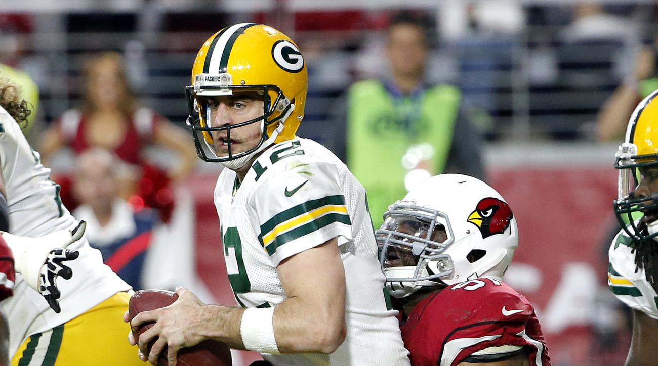Green Bay Packers quarterback Aaron Rodgers (12) is sacked by Arizona Cardinals outside linebacker Alex Okafor (57) during the second half of an NFL football game, Sunday, Dec. 27, 2015, in Glendale, Ariz. (AP Photo/Ross D. Franklin)