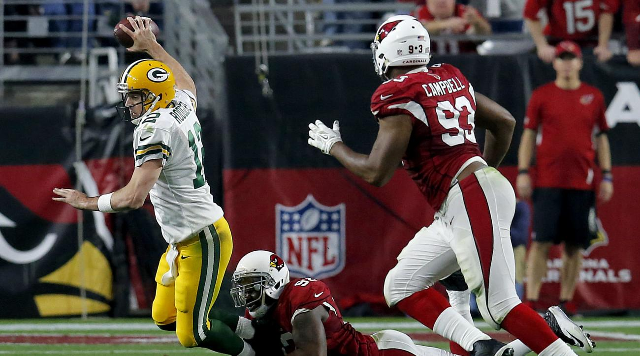 Green Bay Packers quarterback Aaron Rodgers (12) is tackled by Arizona Cardinals defensive end Frostee Rucker (92) during the second half of an NFL football game, Sunday, Dec. 27, 2015, in Glendale, Ariz. (AP Photo/Rick Scuteri)